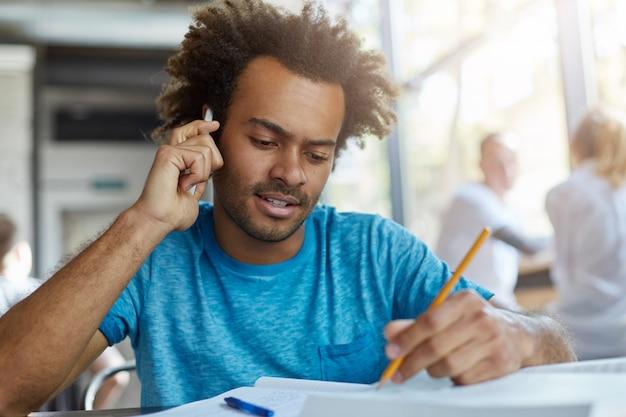 Attraente studente universitario barbuto dalla pelle scura che lavora su un documento del corso nello spazio di coworking, prendendo appunti nel libro di testo con la matita mentre parla con il suo supervisore di ricerca sul telefono cellulare. effetto pellicola