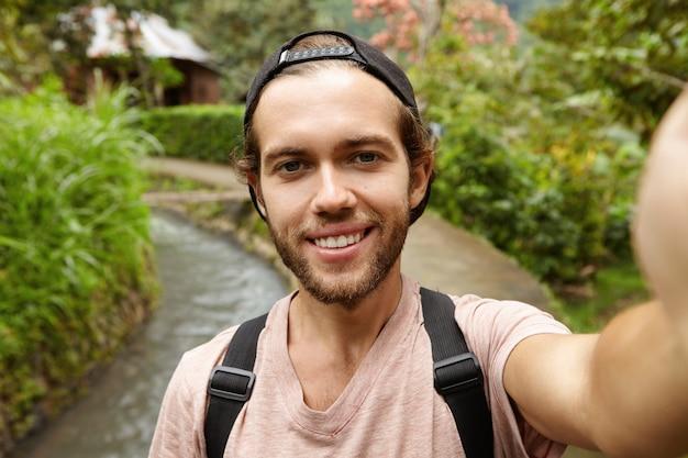 Attraente viaggiatore alla moda con la barba che indossa lo zaino prendendo selfie, in posa sulla strada di campagna. viaggio, avventura