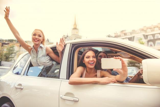 Attraenti ragazze felici in abiti eleganti e occhiali da sole.