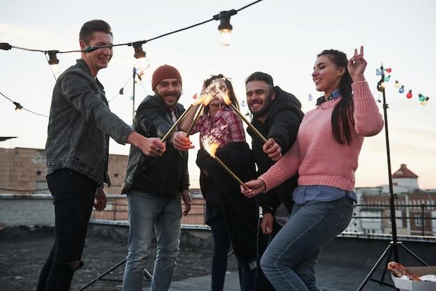Attraversa le fiamme. giocare con le stelle filanti sul tetto. gruppo di giovani amici belli