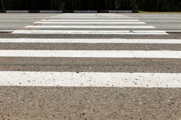 Attraversamento pedonale bianco attraverso la strada.
