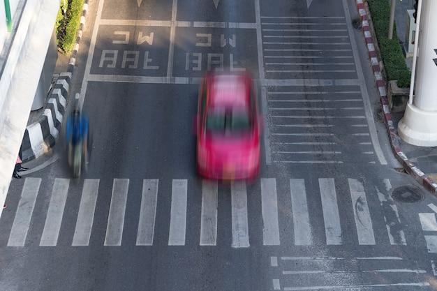 Attraversamento pedonale e auto, strada trafficata della città e auto in motion blur su attraversamento pedonale