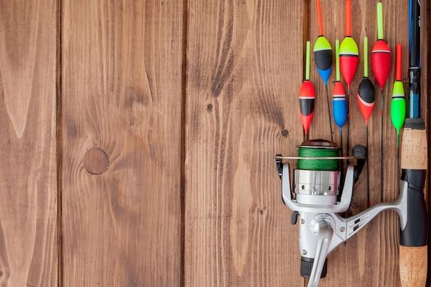 Attrezzatura da pesca - galleggiante e richiami da pesca della canna da pesca su bello fondo di legno blu, spazio della copia