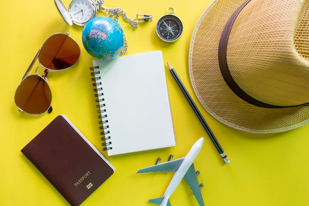 Attrezzatura del viaggiatore su giallo con lo spazio della copia, concetto di viaggio