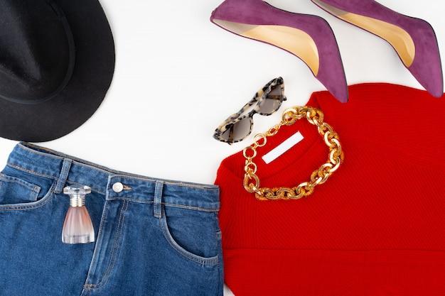 Attrezzatura della donna con il maglione rosso e gli accessori su bianco
