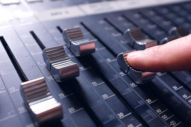 Attrezzatura di amplificazione che regola le manopole e i fader del mixer audio di studio. posto di lavoro e attrezzatura dell'ingegnere del suono. mixaggio acustico di musica, messa a fuoco selettiva.