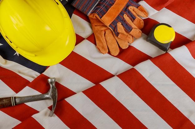 Attrezzatura di strumenti del casco giallo della costruzione di festa del lavoro per la festa federale felice del lavoro sopra sopra la bandiera americana.