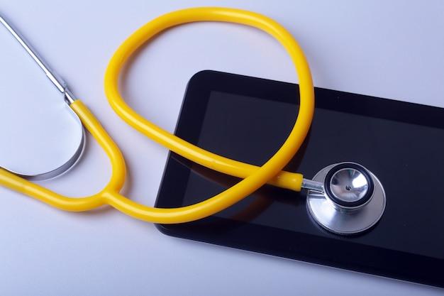 Attrezzatura medica: stetoscopio e compressa blu su fondo bianco