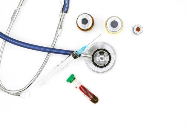 Attrezzatura medica sullo scrittorio, sulle ampolle dello stetoscopio e sulla siringa di medico su fondo bianco con lo spazio della copia, primo piano. concetto di assistenza sanitaria.