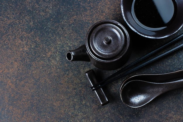 Attrezzatura per alimenti giapponese e cinese sul fondo della tavola concreta di pietra scura. bacchette e tazze di legno con salsa di soia. vista dall'alto con lo spazio della copia