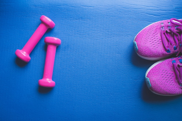 Attrezzatura per la palestra e la testa di legno domestica e le scarpe da tennis sul blu