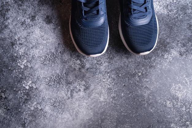 Attrezzature per il fitness con scarpe da ginnastica su sfondo grigio conbcrete, vista dall'alto, copia spazio per il testo.