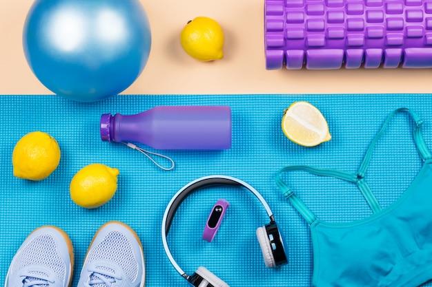 Attrezzature per il fitness. disposizione degli accessori e dei vestiti di allenamento della donna. vista dall'alto, sfondo di fitness