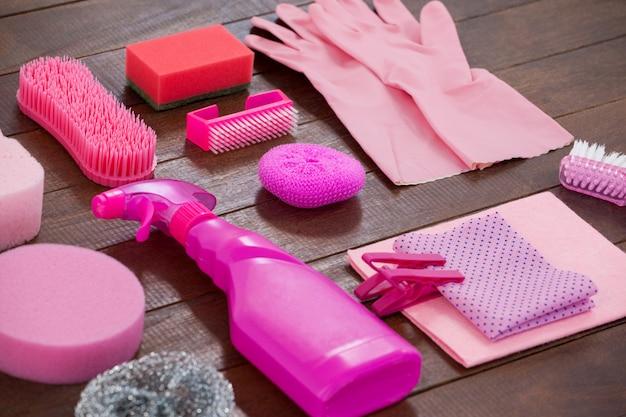 Attrezzature per la pulizia di colore rosa sistemate sul pavimento di legno