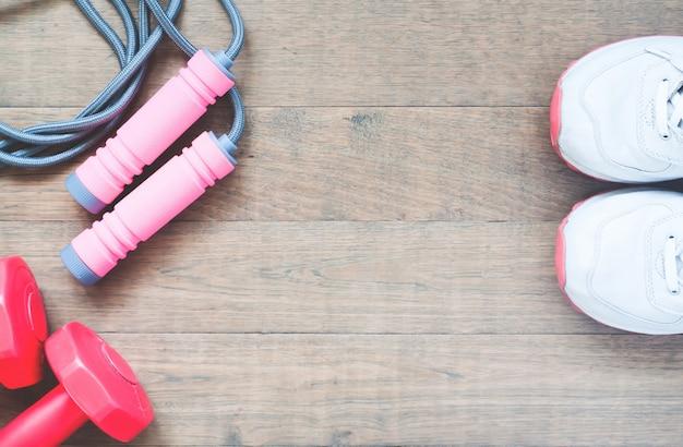 Attrezzature sportive con scarpe sportive su sfondo di legno, stile di vita sano e concetto di lavoro