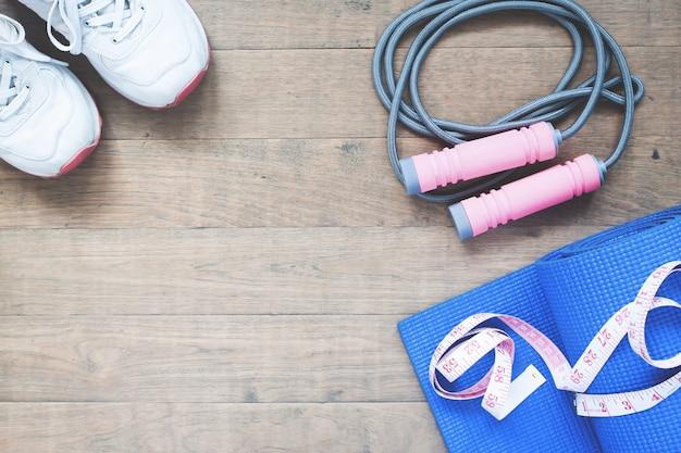 Attrezzature sportive e yoga con nastro di misura su fondo in legno con spazio di copia