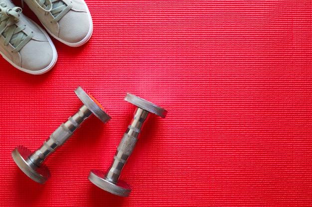 Attrezzature sportive, manubri e scarpe da ginnastica su sfondo rosso. vista piana, vista dall'alto con spazio di copia. stile di vita sano, sport e concetto di perdita di peso