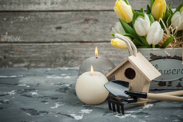 Attrezzi da giardinaggio con fiori e candele accese