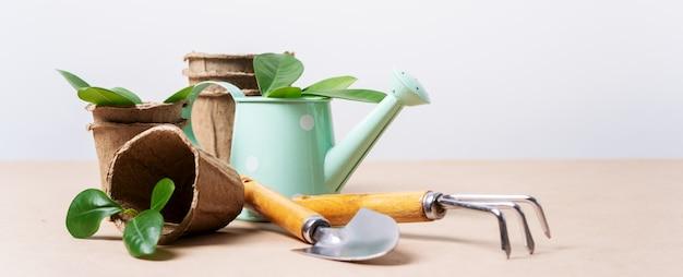 Attrezzi da giardinaggio, vasi di carta, annaffiatoio su carta artigianale con copia spazio.