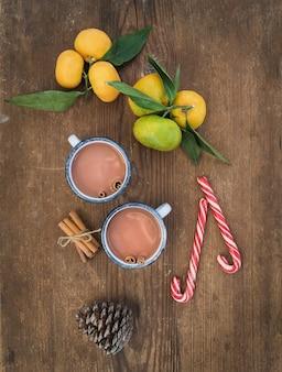 Attributi di natale o capodanno. mandarini freschi con foglie, bastoncini di cannella, pigna, cioccolata calda in tazze e bastoncini di zucchero sul tavolo di legno rustico