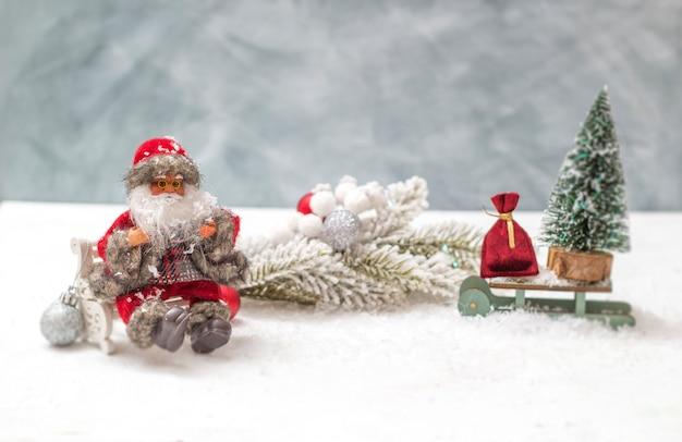 Attributi natalizi: babbo natale, un albero su una slitta e un sacco di giocattoli.