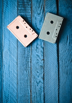 Audio cassetta pastello colorata due su una tavola di legno blu. vista dall'alto, tendenza minimalista
