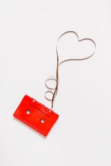 Audio cassetta rossa con nastro a forma di cuore aggrovigliato su sfondo bianco