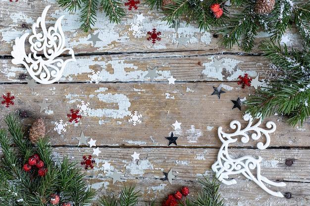 Auguri di buon natale e buone feste, cornice, banner. nuovo anno. carta di felice anno nuovo con neve su fondo in legno. tema di vacanza invernale di natale. lay piatto. copia spazio
