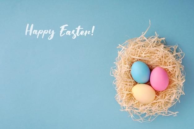 Auguri di buona pasqua; uova colorate in un nido di gallina.