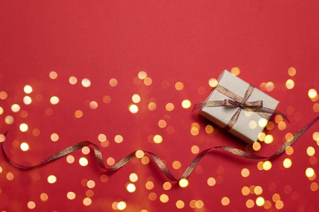 Auguri di buone feste con coriandoli sparkle glitter oro stelle e confezione regalo su sfondo rosso