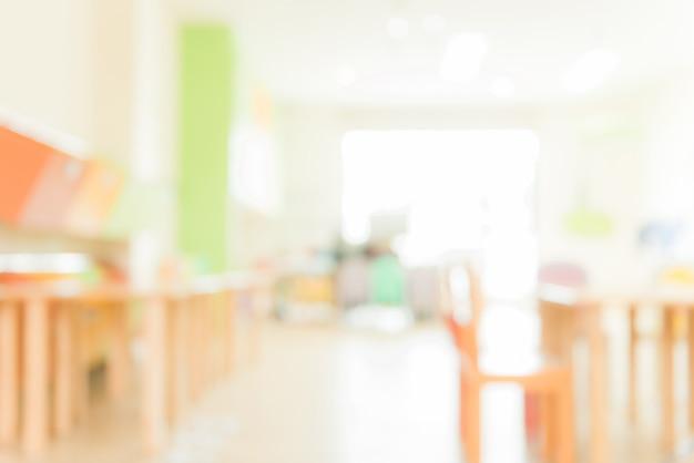 Aula scolara in sfocatura sfondo senza giovane studente; vista sfocata della sala di classe elementare nessun ragazzo o insegnante con sedie e tavoli nel campus. immagini di stile d'effetto vintage.