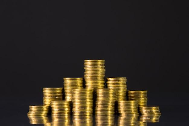 Aumento delle colonne di monete, gradino di pile di monete sul buio