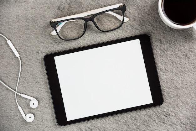 Auricolare bianco; occhiali; tazza di caffè e tablet digitale schermo vuoto sullo scrittorio grigio