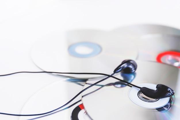 Auricolare nero su compact disc su sfondo bianco