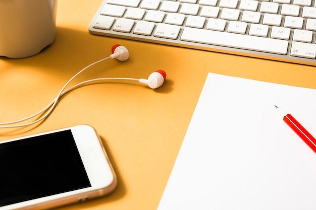 Auricolare; tastiera; carta; matita rossa e cellulare su uno sfondo arancione
