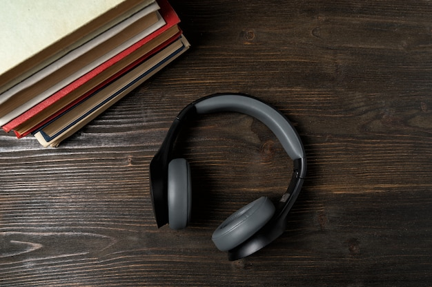 Auricolari e libro. concetto di apprendimento audio. sfondo di legno scuro vista dall'alto