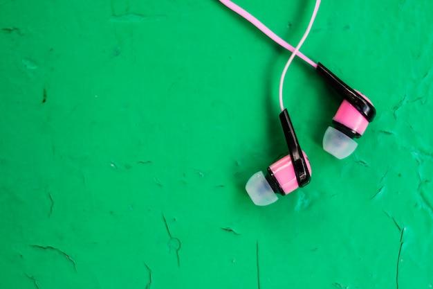 Auricolari stereo rosa su fondo verde in legno