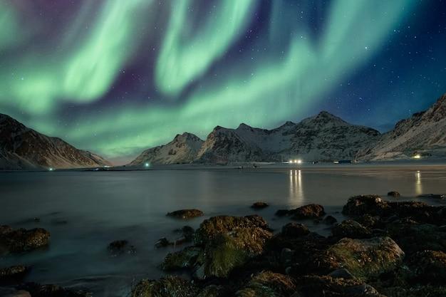 Aurora boreale con stelle sulla catena montuosa