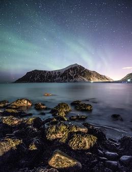 Aurora boreale con stelle sulla montagna con rocce