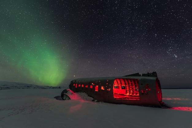 Aurora boreale dell'aurora boreale sopra relitto piano in islanda