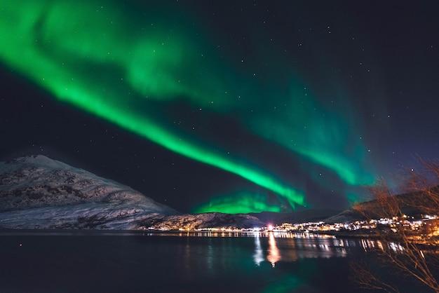 Aurora boreale di fronte al mare con la città sul retro