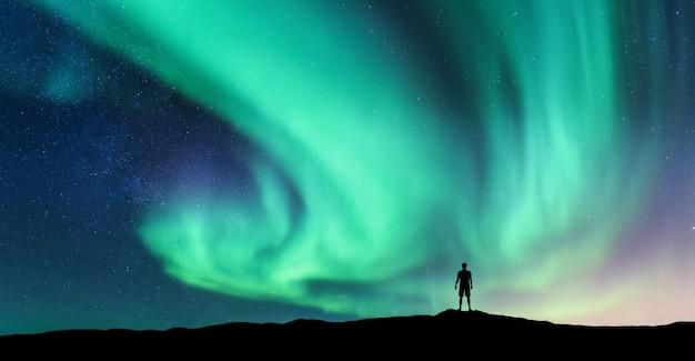 Aurora boreale e silhouette di un uomo in piedi