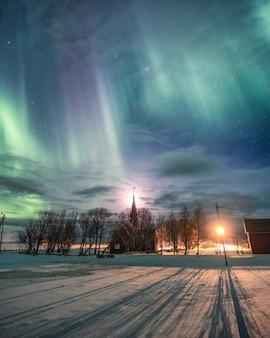Aurora boreale sopra la chiesa cristiana con la luna