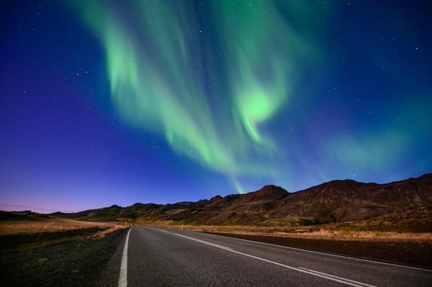 Aurora boreale stupefacente, aurora boreale sulla strada vuota in islanda
