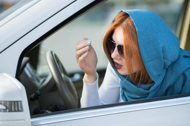 Autista abbastanza alla moda della donna di affari in sciarpa e occhiali da sole che controllano il suo trucco in uno specchio.