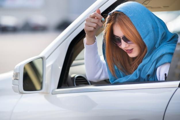 Autista della giovane donna che guarda da un finestrino della macchina