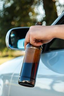 Autista di auto in possesso di una bottiglia di birra