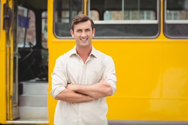 Autista di autobus sorridente che si leva in piedi con le braccia attraversate