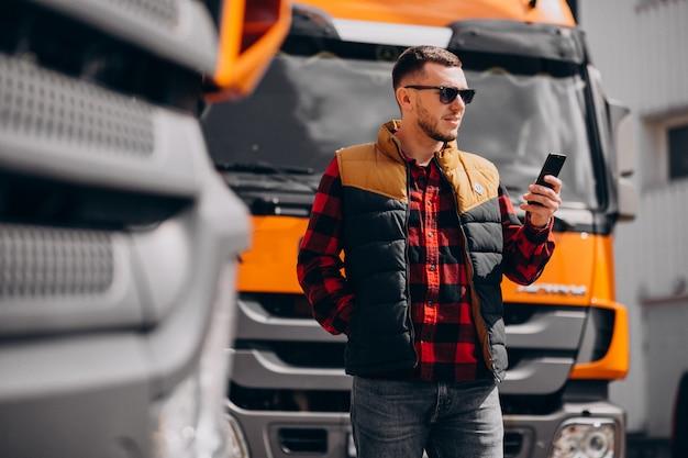 Autista di camion bello dell'uomo che fa una pausa il camion