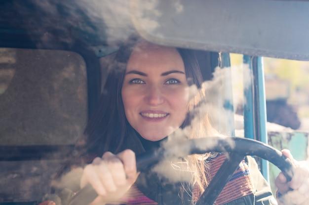 Autista di camion donna in macchina. ragazza che sorride alla macchina fotografica e che tiene il volante.
